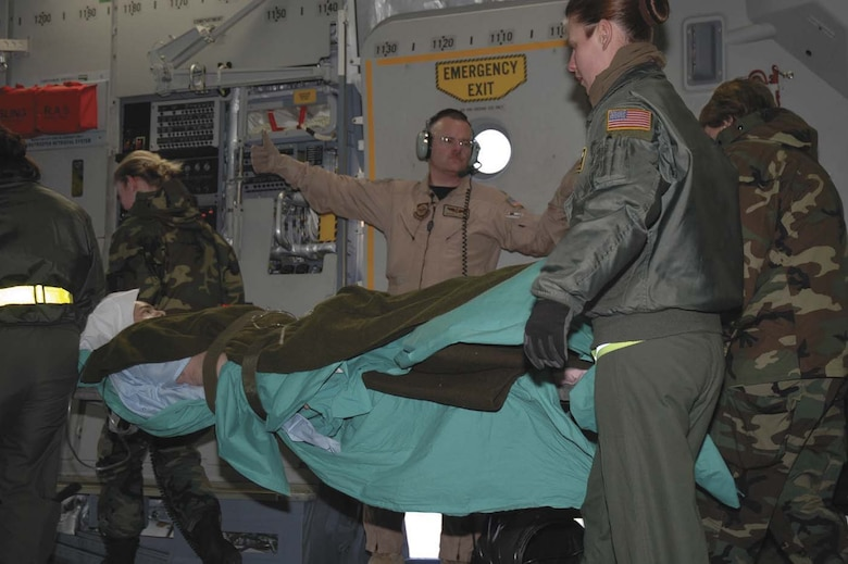 Maj. Gerard Hogan of the 315th Aeromedical Evacuation Squadron, Charleston Air Force Base, S.C., directs the movement of a wounded Soldier being transferred from Iraq to Germany aboard a C-17 Globemaster III. Air Force aeromedical evacuation crews have conducted more than 55,000 patient moves since the beginning of Operation Iraqi Freedom, caring for a wide range of ailments. Nearly 88 percent of the 400 aeromedical evacuation people working worldwide are in Air Force Reserve Command or the Air National Guard, said Lt. Gen. George Taylor, Air Force surgeon general. The 791st Expeditionary Aeromedical Evacuation Squadron at Ramstein Air Base, Germany, the hub for patient movements in Europe and Southwest Asia, is more than 50 percent manned by reserve component people. (1st Lt. Wayne Capps)