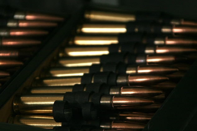 Fifty-caliber rounds are taken from normal 100-round ammo cans, laid out flat and linked together before being put in the 300-round ammo can that the GAU-21 ramp-mounted weapon system shoots from.
