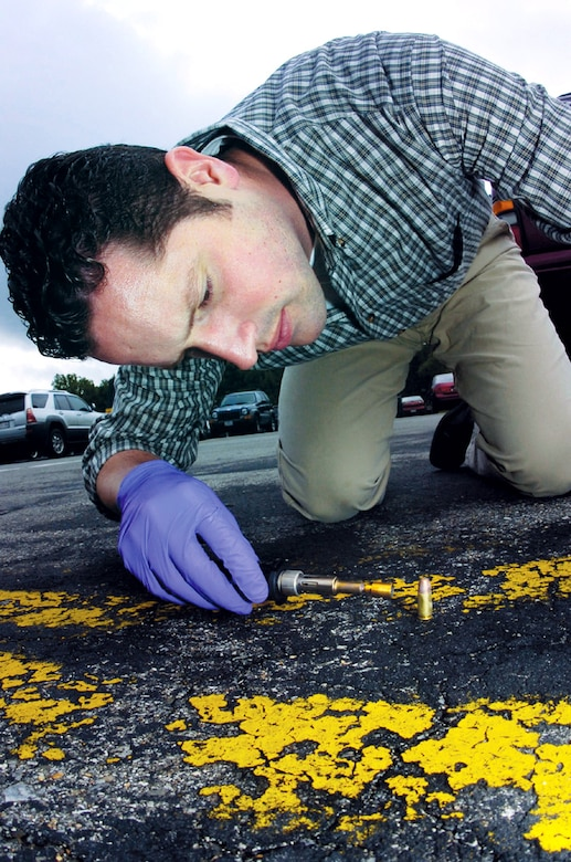 Special Agent Jeremy Gage deposits a gluing agent on a bullet shell to preserve a fingerprint on the shell. Agent Gage is a forensic science consultant with the Air Force Office of Special Investigations' 33rd Field Investigations Squadron. (U.S. Air Force photo/Bobby Jones)