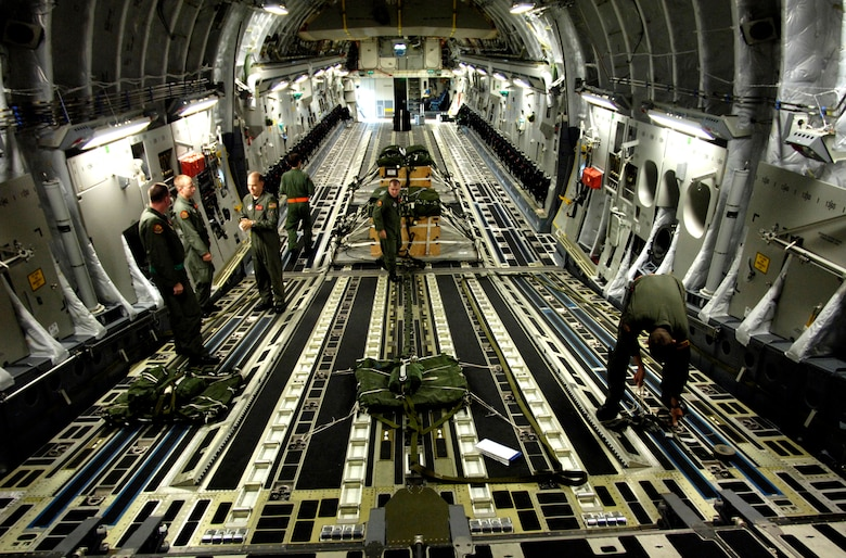 C-17 Globemaster III aircrew members prepare the rigging for parachutes for an upcoming airdrop training mission May 16, 2006, at Hickam Air Force Base, Hawaii. The aircrew members are from the 535th Airlift Squadron. The training provides multi-element training for the pilots enables users to get larger amounts of equipment in a short period of time and maintains aircrew proficiency. (U.S. Air Force photo/Tech. Sgt. Shane A. Cuomo)