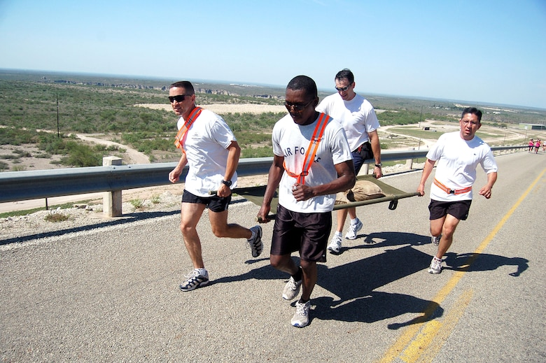 "From left to right, Maj. Dan Pence, Senior Airman Olufemi Owolabi, Col. Mike Minahan, and Tech. Sgt. Gabriel Valdez compete as relay team 'XL1' in the ""sandbag litter carry"" portion of the 7-mile run leg in the 2006 Laughlin Adventure Race.  The third year for the race, it was begun by an instructor pilot at the base as a way to have fun but yet challenge one's self in physical competition.  Major Pence is the wing plans officer, Airman Owolabi works in the public affairs office,  Colonel Minahan is the wing commander and Sergeant Valdez is the wing command post operations NCOIC.  (U.S. Air Force photo/Senior Airman Austin M. May)"