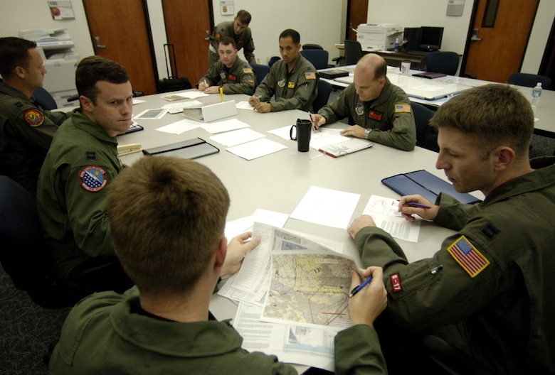 C-17 Globemaster III pilots conduct a pre flight briefing May 16, 2006 before flying a 4-ship airdrop training mission. The pilots are from the 535th Airlift Squadron, Hickam Air Force Base, Hawaii. The 4-ship training provides multi-element training for the pilots enables users to get larger amounts of equipment in a short period of time and maintains aircrew proficiency. (U.S. Air Force photo by Tech. Sgt. Shane A. Cuomo)