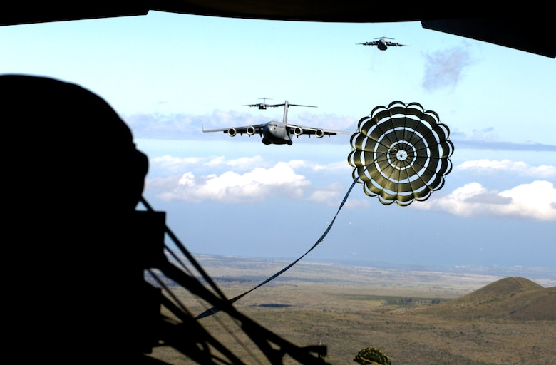 An extraction chute opens over the drop zone during an airdrop training mission on Tuesday, May 16, 2006. The C-17 Globemaster IIIs are from the 535th Airlift Squadron, Hickam Air Force Base, Hawaii.  Base officials are conducting multi-element training for aircrews to maintain aircrew proficiency. (U.S. Air Force photo/Tech. Sgt. Shane A. Cuomo)