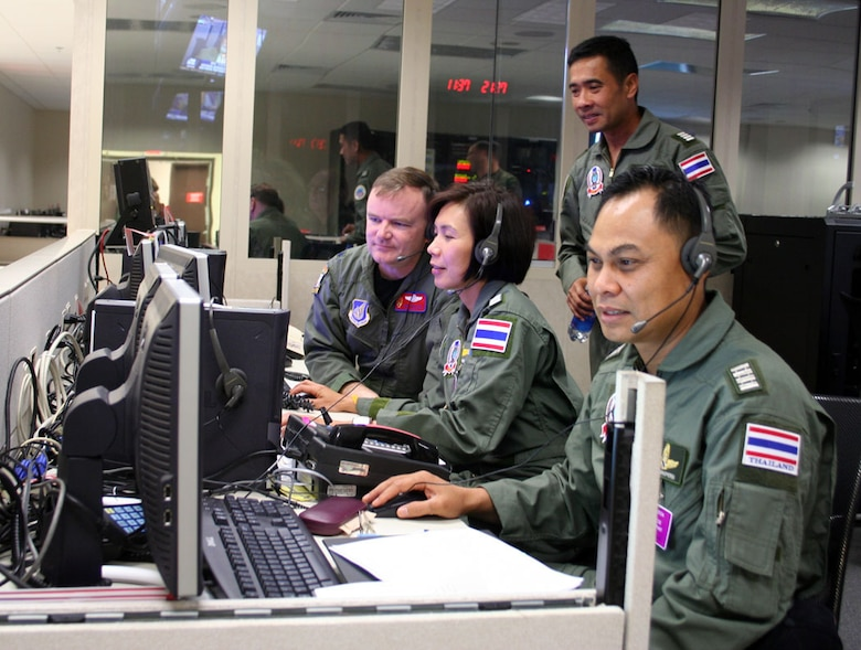 HICKAM AIR FORCE BASE, Hawaii -- Lt Col Curt Walker, Kenney Headquarters (13th Air Force) Pacific Air Operations Center, Combat Operations Division, and Wing Commander Sumana Chulamokha, Group Captain Suwit Wattanaroek (standing), and Group Captain Noi Parkperm from the Royal Thai Air Force coordinate air operations in KHQ's PAOC during the 25th annual Cobra Gold exercise hosted by Thailand. The exercise demonstrated the planning, execution and reach back capabilities KHQ can provide to the Combined Forces Air Component Commander during a joint and/or combined contingency. (Courtesy photo)