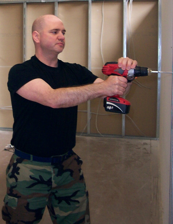 Master Sgt. Chuck Drake, NCO in charge of Civil Engineer Operations for Detachment 1, 460th Space Communications Squadron, drills a hole to cut a doorway for a new classroom at an off-base church he attends here. Sergeant Drake volunteers at the church during his off-duty time. (Courtesy photo)