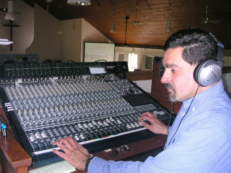 Mr. Hector Camacho, contract employee with Detachment 1, 460th Space Communications Squadron, runs an equipment check on the sound system at the off-base church he attends. He serves as a deacon and chairperson of the audiovisual committee at the church. (Courtesy photo)