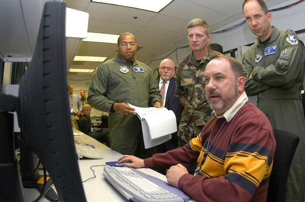 Dan Ingald demonstrates the Advanced Extremely High Frequency Satellite Mission Control Segment's test, training and simulation software to Lt. Col. Keith Phillips, Air Force Space Command Directorate of Plans and Requirements; Col. William Harding, Space and Missile Systems Center; and Lt. Col. John Shaw, 4th Space Operations Squadron commander. Mr. Ingald is the AEHF Test and Training Test Lead at Lockheed Martin. (U.S. Air Force photo by Staff Sgt. Don Branum)