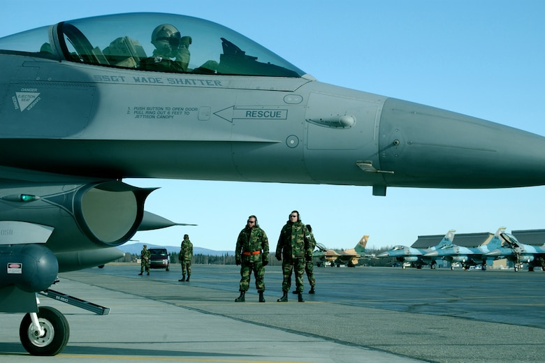 EIELSON AIR FORCE BASE, Alaska -- Crew chiefs from the 175th Fighter Squadron, South Dakota Air National Guard, look on while 2nd Lt. Travis Boltjes, 175th FS pilot, goes through his final checks in his F-16 Fighting Falcon here during RED FLAG-Alaska 06-2 May 2, 2006. (Air Force photo by Tech. Sgt. Sara Hilmoe)
