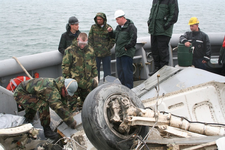 IN THE WEST SEA, Republic of Korea ? Staff Sgt. Ryan Aday (far left), crash recovery, searches for a flight data recorder among F-16 wreckage salvaged by Navy divers. The wreckage from the March 14 crash was recovered by the U.S.S. Safeguard May 10 and will assist in the investigation. (Photo by Staff Sgt. Melissa Allan)