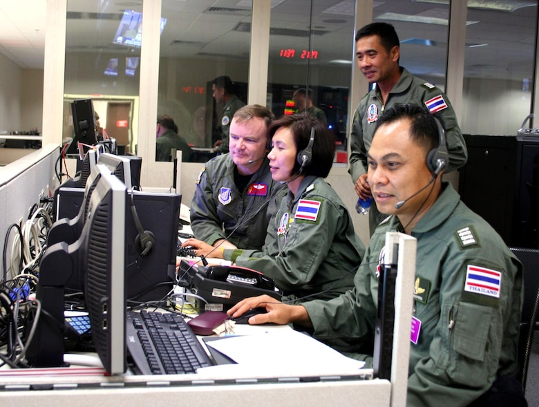 Lt. Col. Curt Walker (left), Wing Commander Sumana Chulamokha, Group Capt. Suwit Wattanaroek (standing) and Group Capt. Noi Parkperm coordinate air operations at the Gen. George C. Kenney Headquarters during the 25th annual Cobra Gold exercise on Tuesday, May 23, 2006. The exercise is hosted by Thailand at Hickam Air Force Base, Hawaii, from May 15 to 26. It demonstrates the planning, execution and reach-back capabilities the headquarters can provide in a contingency. Colonel Walker is with the combat operations division at Kenney Headquarters and the three Thai officers are with the Royal Thai Air Force. (U.S. Air Force photo/Capt. Yvonne Levardi)
