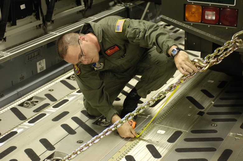 HICKAM AIR FORCE BASE, Hawaii -- Master Sgt. Mike Cumberland, a C-17 loadmaster with the 535th Airlift Squadron, Hickam AFB Hawaii, measures a tie-down chain to ensure a Halvorsen aircraft pallet loader is safely secured prior to a strategic airlift mission May 25.  Hickam sent two C-17s and approximately 25 personnel to assist the Australian Defense Force move personnel and equipment to Australia from the Solomon Islands to support peace operations in East Timor after continued unrest between East Timorese military forces and breakaway groups of police and military.  (U.S. Air Force Photo by Tech. Sgt. Shane Cuomo)