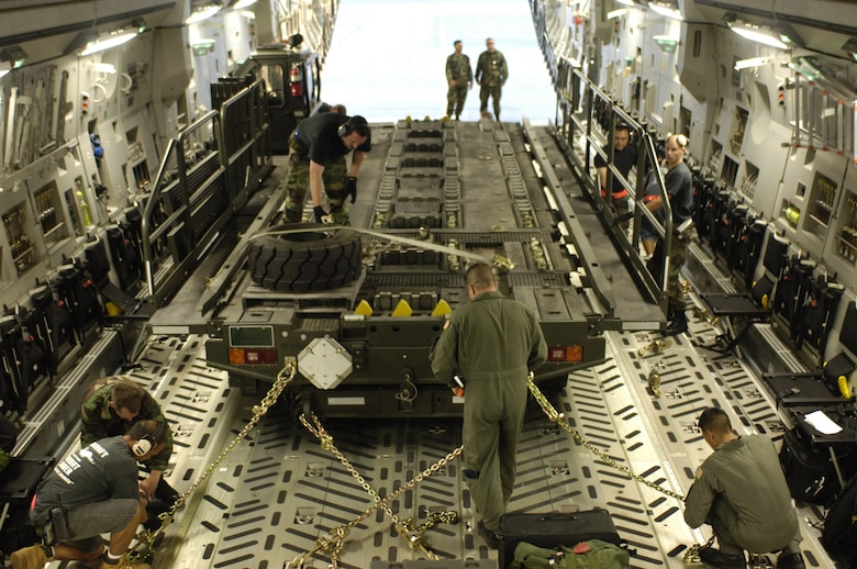 HICKAM AIR FORCE BASE, HAWAII -- Aircrew members and aerial port specialists  secure a Halvorsen aircraft pallet loader in a C-17 at Hickam Air Force Base, Hawaii, May 25.  Hickam sent the loaders along with two C-17s and approximately 25 personnel to assist the Australian Defense Force move personnel and equipment to Australia from the Solomon Islands in support of peace operations in East Timor after continued unrest between East Timorese military forces and breakaway groups of police and military. (U.S. Air Force Photo by Tech. Sgt. Shane Cuomo)