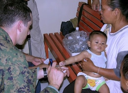 SEWON, Indonesia (May, 31, 2006) -- Navy Lt. Tim Ayers examines a 12-month-old Indonesian girl at a clinic established here today by III Marine Expeditionary Force Marines and sailors at the request of the Indonesian government following the May 27 earthquake that tore through the island of Java. The team of about 100 service members is providing surgical and acute care for victims. The infant was struck in the back by a falling brick during the earthquake. (Official U.S. Marine Corps photo by 1st Lt. Eric C. Tausch)