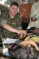 BANTUL, Indonesia ? Lt. Cmdr. Carlos Godinez checks the pulse of Siti Nuriyami, in Bantul, Indonesia, May 31 after a 6.2 magnitude earthquake struck the island of Java. Nuriyami suffered broken ribs and a arm during the earthquake. Godinez is a III Marine Expeditionary Force surgeon. (Official U.S. Marine Corps photo by Lance Cpl. Warren Peace)