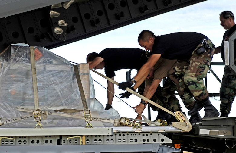 Airmen from the Combat Mobility Element, or CME, push a cargo pallet onto a C-17 Globemaster III at Royal Australian Air Force Base Townsville, Australia, on Tuesday, May 30, 2006. The CME is part of the 15th Logistical Readiness Squadron at Hickam Air Force Base, Hawaii. The CME is in Townsville to help prepare and load equipment on C-17s from Hickam that are repositioning Australian Defense Forces to better support peace operations in East Timor. (U.S. Air Force photo/Tech. Sgt. Shane A. Cuomo)