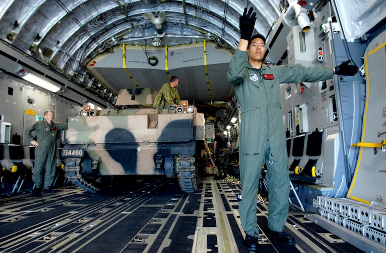 Airman James Ngo marshals in a second armored personnel carrier onto a C-17 Globemaster III at Royal Australian Air Force Base Townsville, Australia, on Tuesday, May 30, 2006. Two C-17s from the 15th Airlift Wing and the Hawaii Air National Guard's 154th Wing at Hickam Air Force Base, Hawaii, are helping the Australian Defense Force reposition its forces in Australia to better support peace operations in East Timor. Airman Ngo is assigned to the 535th Airlift Squadron. (U.S. Air Force photo/Tech. Sgt. Shane A. Cuomo)