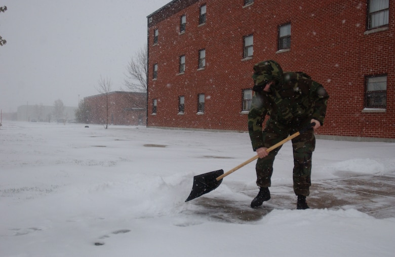 Senior Airman Andrew Close, 5th Communications Squadron, shovels snow in front of the 5th CS dorms during a snowfall on October 30. The base recived about three inches of snow. (U.S. Air Force photo by Airman Sharida Bishop)