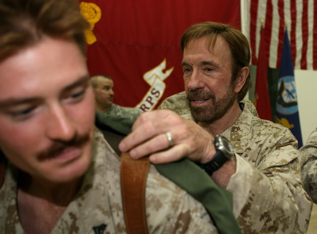 Martial arts expert and action film star, Chuck Norris signs a T-shirt for Cpl. William P. Kessler, 23 of Cedar Park, TX. Kessler, a reconnaissance Marine with Company A, 3rd Reconnaissance Battalion from Okinawa, Japan. Norris and fellow actor Marshall Teague toured camps throughout Al Anbar province and Kuwait as a part of their United Service Organization sponsored trip. The action stars hoped to raise the morale of the troops, give inspirational speeches, and provide a handshake with a smile. They made Camp Fallujah their ninth stop of 11, finishing up their tour with stops in Camps Ramadi and Taqaddum to visit the troops there. â??I came here to see the morale of the troops and to give them a morale boost,â? said Norris. â??If it helps them in any way positively, Iâ??m elated.â? Photo by Cpl. Lynn Murillo