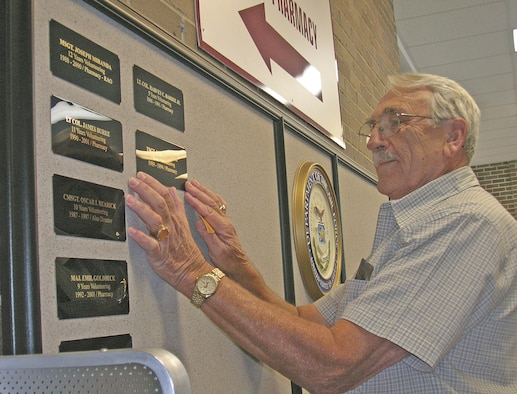 (Ret.) Technical Sgt. Ebert Bailey places the names plates on the volunteer wall memorial in preparation for the unveiling by the wing commander held Oct. 27.  The memorial is located in the main lobby of the base exchange and in front of the satellite pharmacy. (U.S. Air Force photo by Robin DeMark)