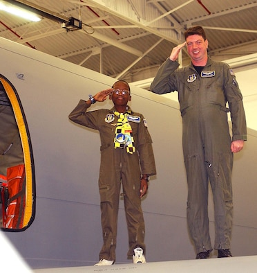 """ANDREWS AIR FORCE BASE, Md. -- Michael Ogunjimi, 10, of Washington, D.C., joins Reservist Capt. Scott Clark, 756th Air Refueling Squadron pilot, to salute from the wing of a KC-135 Stratotanker Oct. 27. The 459th Air Refueling Wing and the District of Columbia Air National Guard 113th Wing teamed up to host the """"Pilot for a Day"""" program. """"P4D"""" is a community outreach program that allows military and civilian children of all ages who suffer from serious or chronic medical conditions to visit an installation for the day to tour wing and base facilities. (U.S. Air Force photo by Staff Sgt. Amaani Lyle)"""