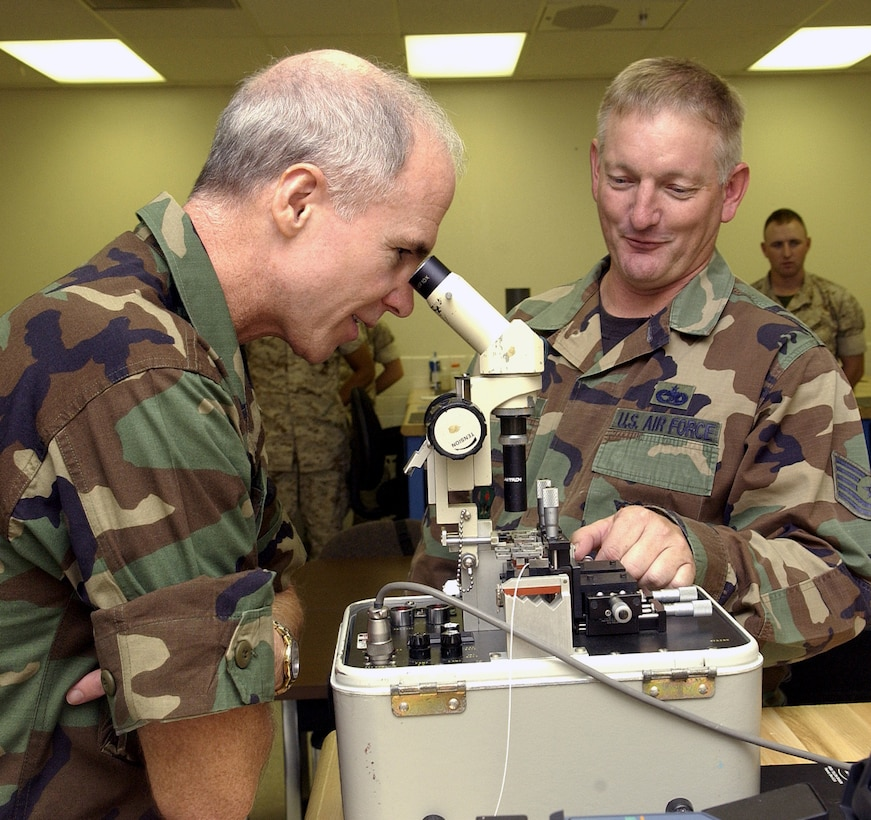 Brig. Gen. Richard Devereaux, 82nd Training Wing commander, looks into a fiber optic fusion splicer as Tech. Sgt. Steven Baker, an instructor at the 364th Training Squadron, explains how the machine works. (U.S. Air Force photo/Mike Litteken)