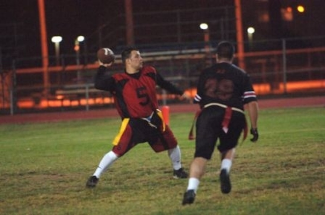 Mike Averill, 728th Air Mobility Squadron quarterback, drops back to pass the ball while under hot pursuit during a regular season flag-football game here. (Courtesy photo)