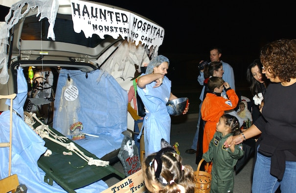 Staff Sgt. Amber Campbell, 31st Medical Operations Squadron, takes care of her 'patients' at the 'Haunted Hospital' during  Trunk or Treat Oct 27. Aviano members decorated their vehicles  in spooky designs for the Trunk or Treaters to enjoy.  (Photo by Airman First Class Liliana Moreno)