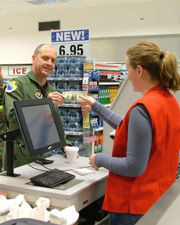 Col. Monty Brock, 31st Fighter Wing vice commander, makes the first purchase at Aviano's new shoppette in the flightline area.  The shoppette is open Mondays through Thursdays from 6 a.m. to 10 p.m., Fridays from 6 a.m. to midnight, Saturdays from 8 a.m. to midnight, and Sundays from 8 a.m. to 10 p.m. (Photo by Senior Airman Colleen Wieman)