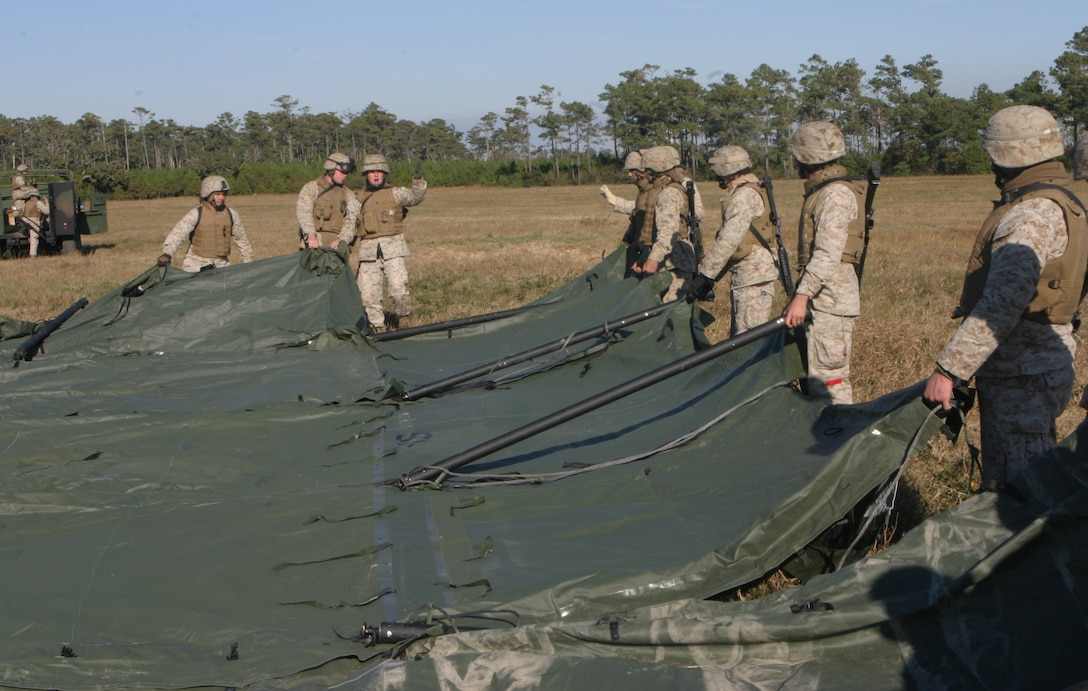 Marines from the 26th Marine Expeditionary Unit's Combat Logistics Battalion-26 build tents to house displaced persons during a humanitarian assistance drill, Nov 4, 2006.  The II Marine Expeditionary Forces Special Operations Training Group graded the CLB-26 on its proficiency in building the camp and managing the affected population who would use the facility after its construction.