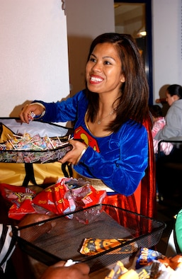 Tech. Sgt. Sheila White, 30th Mission Support Squadron, passes out candy to  children at the deployed spouses halloween costume party on Oct. 26, at the Breakers Dinning Facility here. The party was sponsored by the Family Support Center and the 30th Services Squadron to help keep moral high and bring the families of deployed troops together. (U.S. Air Force photo/Airman Nichelle K. Griffiths)