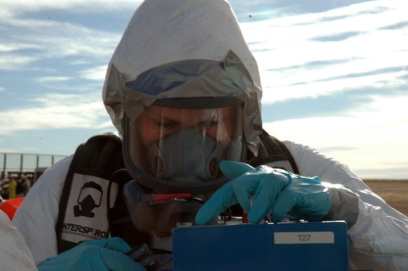 BUCKLEY AIR FORCE BASE, Colo. -- Senior Airman Jessica Mueller, 460th Medical Group Bioenvironmental Flight, programs the high volume air sampler, which samples airborne alpha radiation at the center of a contamination point during an exercise here Nov. 7. Members of the 460th Civil Engineer Squadron Emergency Management Flight, 460th Medical Group Bioenvironmental Flight and 460th CES Fire Protection Flight exercised their ability to move people from a contaminated area into an uncontaminated area through a decontamination line. (U.S. Air Force photo by Staff Sgt. Sanjay Allen)