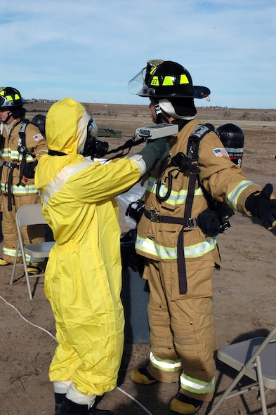 BUCKLEY AIR FORCE BASE, Colo. -- Airman 1st Class R.J. Cockrell, 460th Civil Engineer Squadron Emergency Management Flight, checks the fire suit of Mr. Chris DeBaca, 460th CES Fire Protection Flight, for alpha radiation at the decontamination point during an exercise here Nov. 7. Members of the 460th Civil Engineer Squadron Emergency Management Flight, 460th Medical Group Bioenvironmental Flight and 460th CES Fire Protection Flight exercised their ability to move people from a contaminated area into an uncontaminated area through a decontamination line. (U.S. Air Force photo by Staff Sgt. Sanjay Allen)