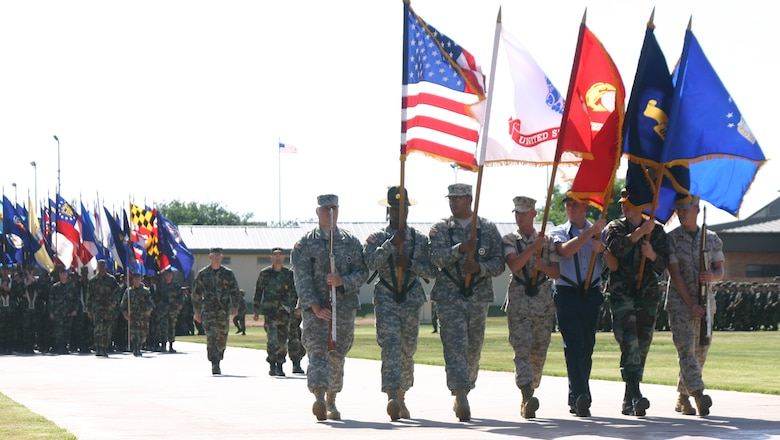 Airmen, Sailors, Soldiers and Marines carry the colors May 20 during the Armed Forces Day parade at the new parade ground. (U.S. Air Force photo/John Ingle).