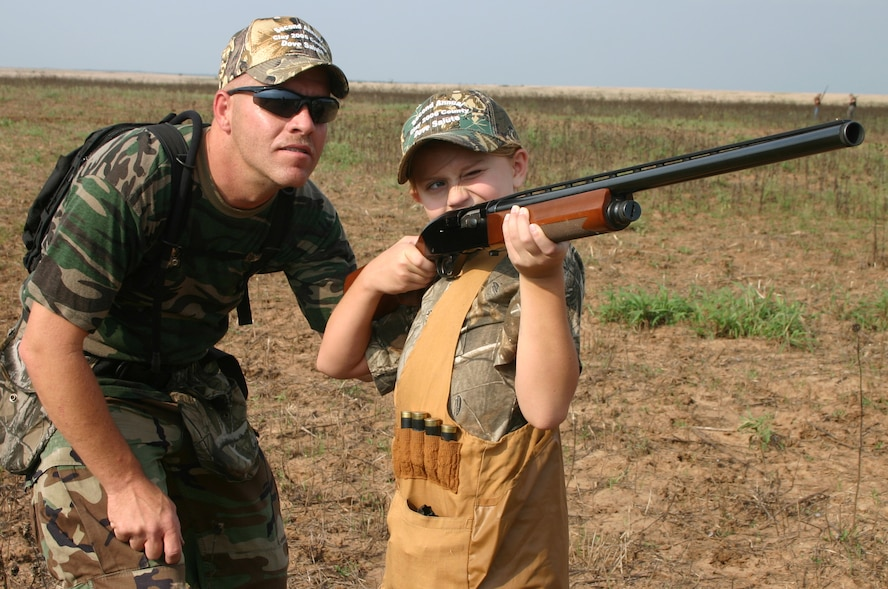 Robert Heis, from the 982nd Maitenance Squadron, watches as his daughter Elizabeth Heis takes aim Saturday at the second annual Clay County Dove Hunt Salute to the Military at the Birdwell and Clark Ranch in Henrietta, Texas. Participants were treated to dove hunting, skeet shooting and steak dinner, free of charge. (U.S. Air Force photo/Mike McKito)