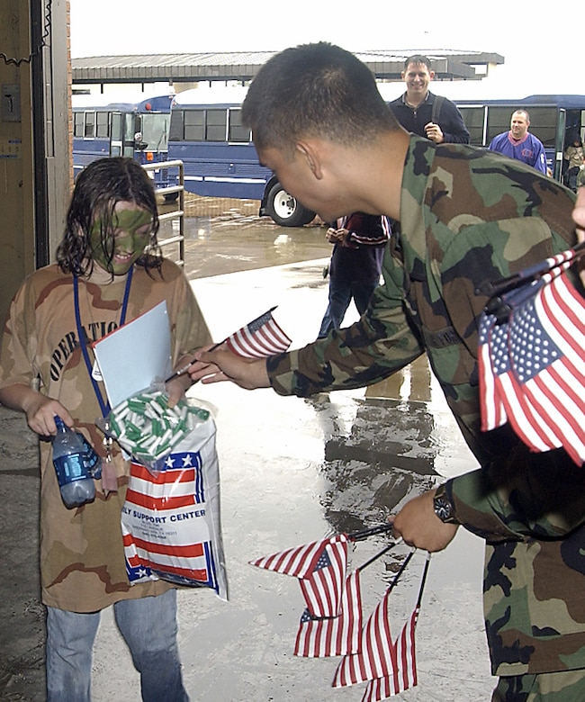 """A Team Sheppard member welcomes home a participant in Saturday's Operation Kids 2006 after a """"lenghty deployment"""" to Camp Liberty. About 150 children of Team Sheppard personnel braved the weather, processing lines, briefings and MREs to experience what takes place when preparing for a deployment. (U.S. Air Force photo/Mike Litteken)."""