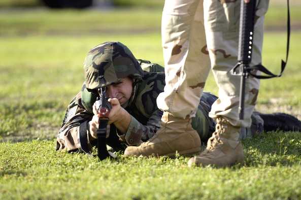 A student attending the Expeditionary Combat Skills Training Course Nov. 3 at Hickam Air Force Base, Hawaii, fires from the prone position during an individual movement techniques class as an instructor observes.  (U.S. Air Force photo/Tech. Sgt. Shane A. Cuomo)