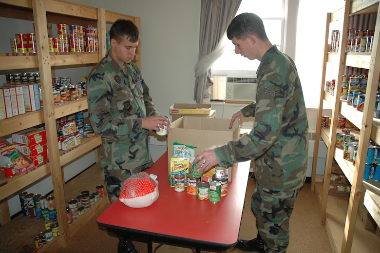 Airman Michael Hanselman (left),  and Airman 1st Class Benjamin Lee (right), both 791st Missile Security Forces Squadron, put together Thanksgiving Day baskets at the First Sergeant's Food Pantry Tuesday. The baskets include a complete Thanksgiving Day dinner and will be distributed by the First Sergeants Nov. 17. (U.S. Air Force photo by Airman Wesley Wright)