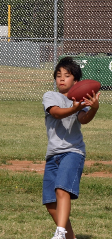 Ryan Stevens catches the ball during a flag football game at the youth centers summer sports camp. (U.S. Air Force photo/Amn Jacob Corbin).