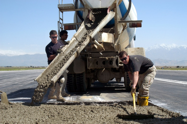 Tech. Sgt. John Foster (left) pours concrete on the active runway at Bagram Air Base, Afghanistan, as part of a $2.3 million airfield repair project. Tech. Sgt. James Holman spreads concrete in a hole. The runway project was one handled by Robert Owens, a civilian with the Tulsa Branch of the Army Corps of Engineers here. (U.S. Air Force photo/Tech. Sgt. Adam Johnston).