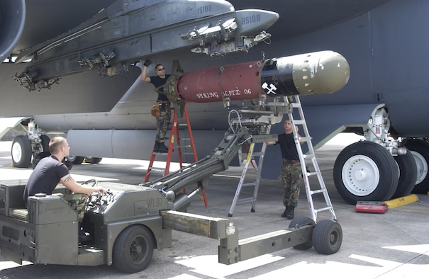 ANDERSEN AIR FORCE BASE, Guam – Staff Sgt. Joshua Sweet (right) gives directions to Airman 1st Class Wayne Robinson (left) while positioning a Mk 56 mine under the wing of a B-52 Stratofortress.  Once in position, SSgt Jason Smith (middle) and Sergeant Sweet will secure the weapon to the heavy stores adapter beam.  These 36th Expeditionary Aircraft Maintenance Squadron weapons loaders were critical in the success of a joint week-long mine exercise which concluded Nov 3.  (U.S. Air Force photo by Staff Sgt. Eric Petosky)