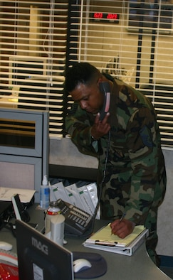 Master Sgt. Michael Williams logs a phone call Tuesday at the base's command post. (U.S. Air Force photo/John Ingle).