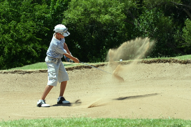 Taylor Schoppa, 12 years old, pitches out of a sand trap during the Texas-Oklahoma Junior Golf Tournament at Wind Creek Golf Course Monday. Schoppa said he came out to the tournament to see how he would play against other competitors.  (U.S. Air Force photo/Airman Jacob Corbin).
