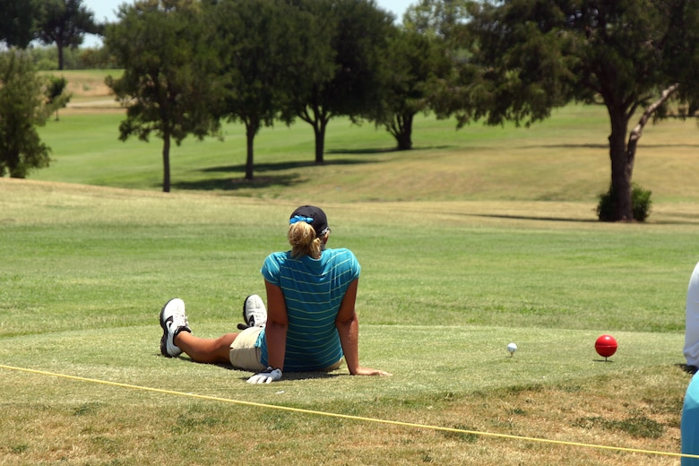 participant in the Texas-Oklahoma Junior Golf Tournament Monday rests while waiting to tee off.  (U.S. Air Force photo/Airman Jacob Corbin).
