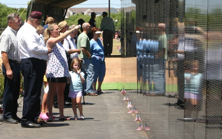 Images of the present merge with those of the past as a family visits the Vietnam Moving Wall Sunday at Crestview Memorial Park in Wichita Falls. The wall is a replica of the Vietnam Veterans Memorial in Washington, D.C. Drivers take the wall around the country to remind those of the lives lost during the Vietnam War. (U.S. Air Force photo/Senior Airman Tonnette Thompson).