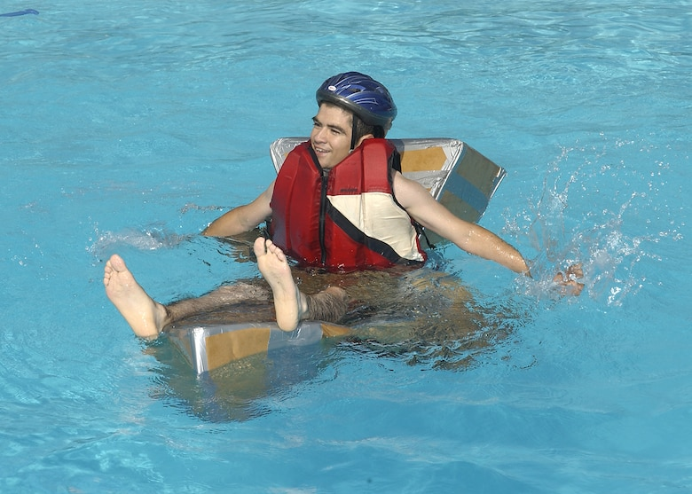 A participant in the cardboard boat race Saturday attempts to maneuver a quickly sinking entry to the end of the pool and back. (U.S. Air Force photo/Mike Litteken).