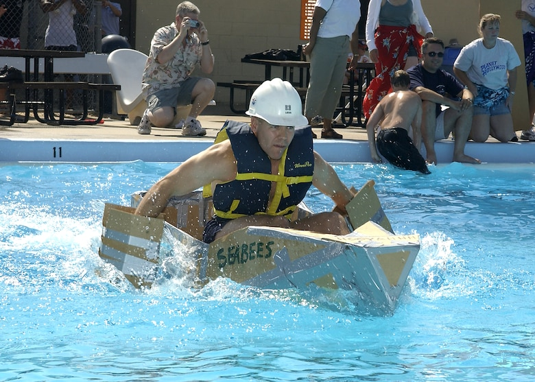 Steve Legg propels the Nave Seabee team cardboard boat across the main pool at the cardboard boat race Saturday. The Seabees duct-taped paddles they built from spare boat-making materials to his hands, eschewing the standard canoe paddle given to all the teams. (U.S. Air Force photo/Mike Litteken).