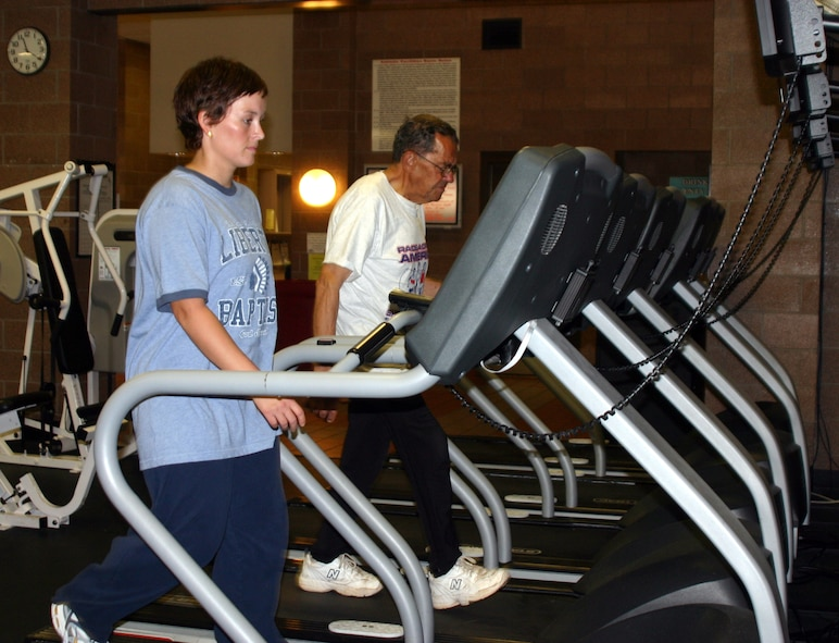 Amy Preskitt and Donnie Dow walk on treadmills at the Levitow Fitness Center Tuesday. Preskitt and Dow are the first participants in the Race Across America fitness event to reach the 500-mile mark. (U.S. Air Force photo/Airman Jacob Corbin)