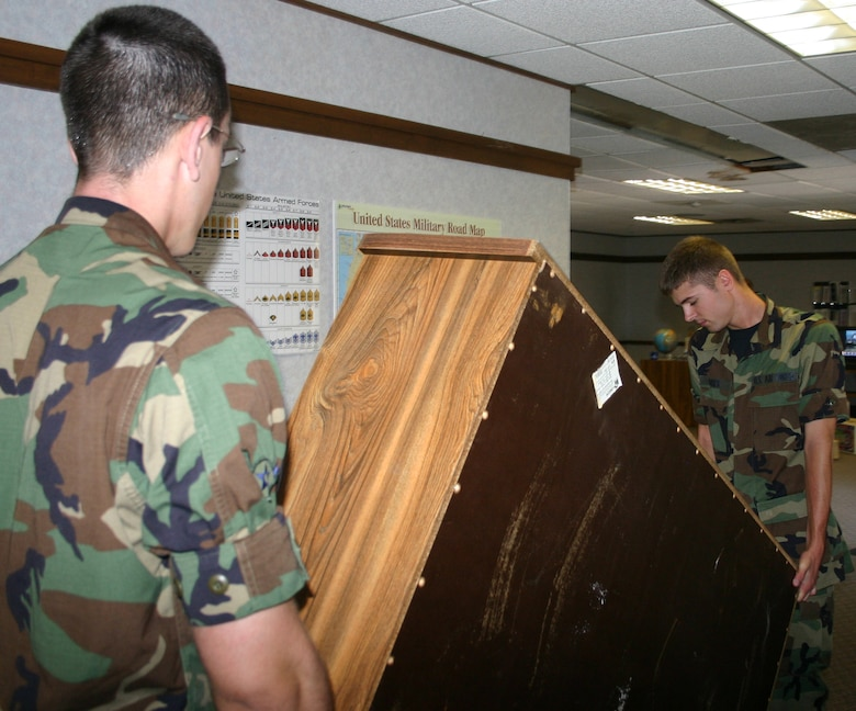 Airmen from the 362nd Training Squadron move a shelf from the old family support center to the new facility in Bldg. 962. (U.S. Air Force photo/Robert Fox)