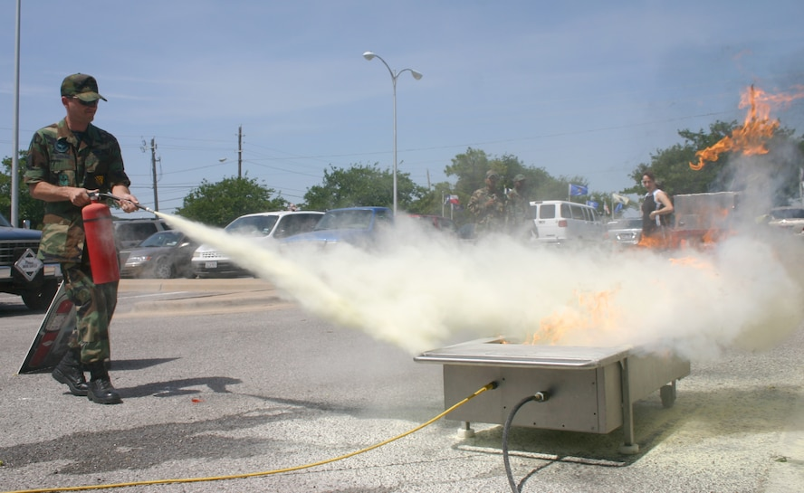 Staff Sgt. Jonathan Murkins, from the 360th Training Squadron, puts out a controlled fire with a fire extinguisher as part of the Sheppard Fire Department's display and briefing during the Safety Day Fair May 26. Members of the fire department trained spectators on how, where and when to use different types of extinguishers. (U.S. Air Force photo/Senior Airman Jacque Lickteig).