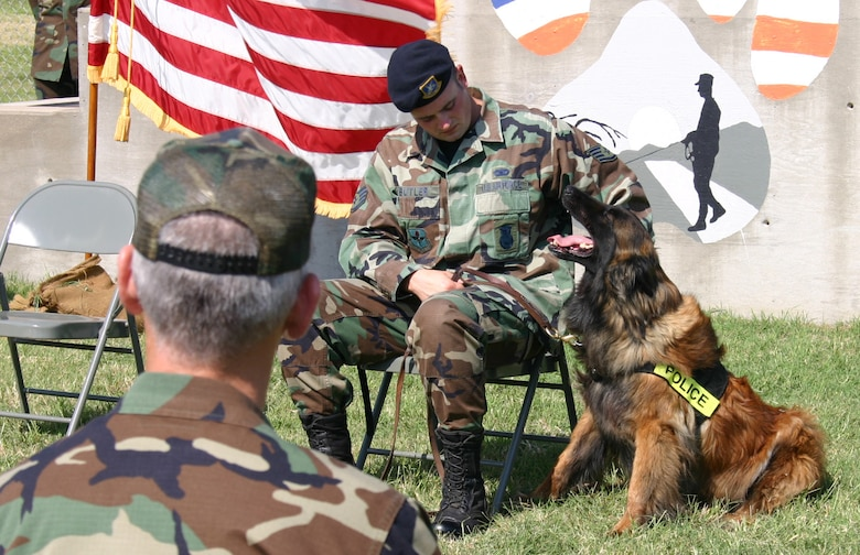 Staff Sgt. Thomas Butler, from the 82nd Security Force Squadron, pets Charque, his military working dog, during the dog's retirement ceremony May 25. Charque served for eight years. (U.S. Air Force photo/Staff Sgt. Jennifer Baxter).